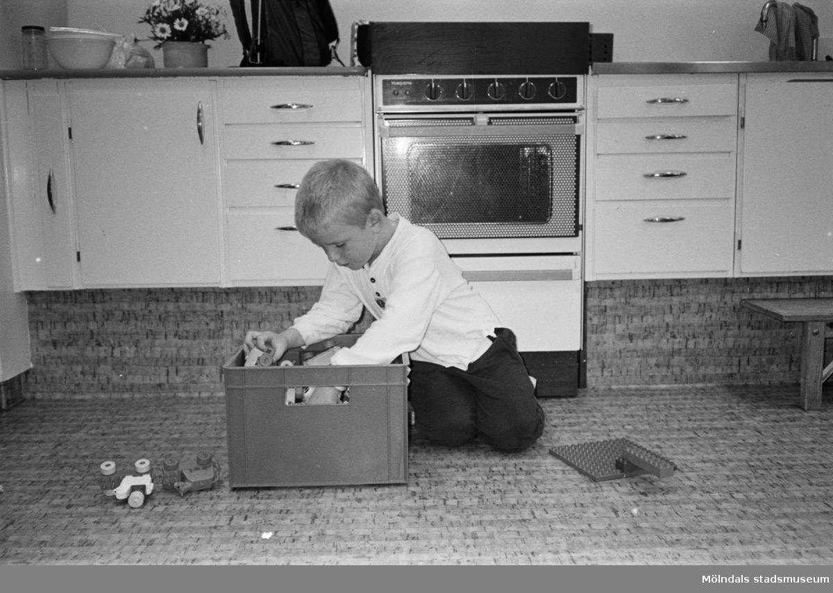 Pontus sitter på köksgolvet och letar runt i en plastback som är fylld med duplo-lego. En byggplatta och ett par duplo-bilar ligger på golvet. Hoppetossan, Katrinebergs daghem, 1992.