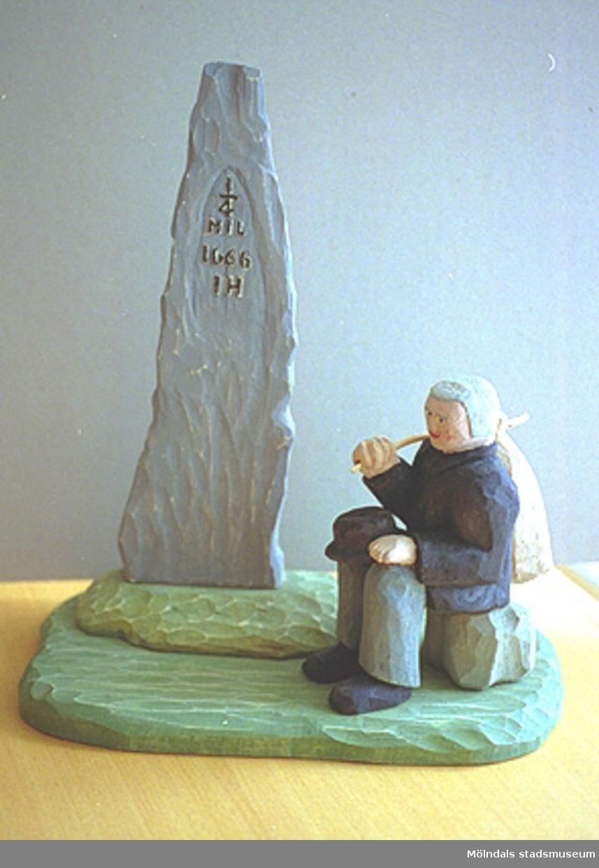 """En äldre man sitter på en sten. Han håller en svart hatt i ena handen och en kappsäck över axeln i den andra. Vid sidan av står ett hög spetsig sten med inskriptionen: """"1/4 mil 1666 IH"""". Harry Bergmans """"gubbar"""" (träfigurer)."""