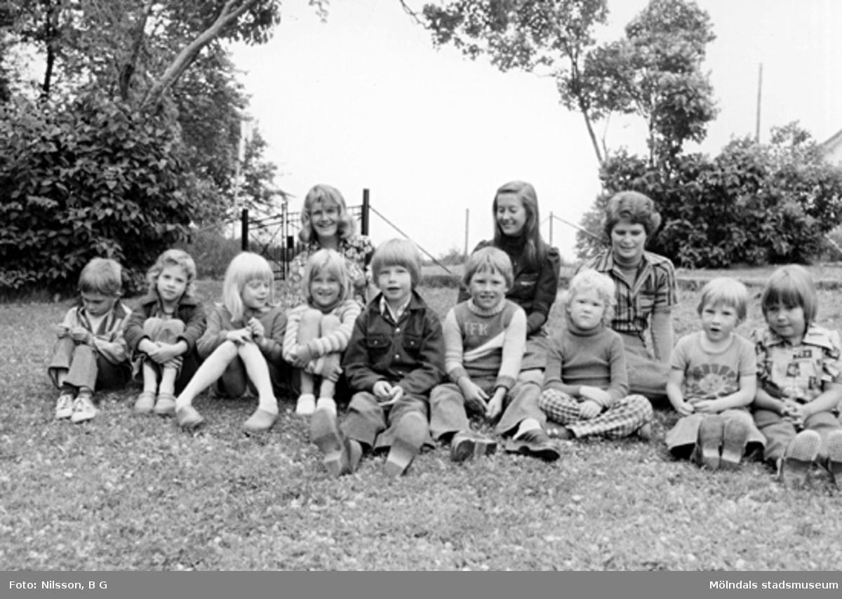 Några barn och tre fröknar sitter i gräset. Holtermanska daghemmet 1973.