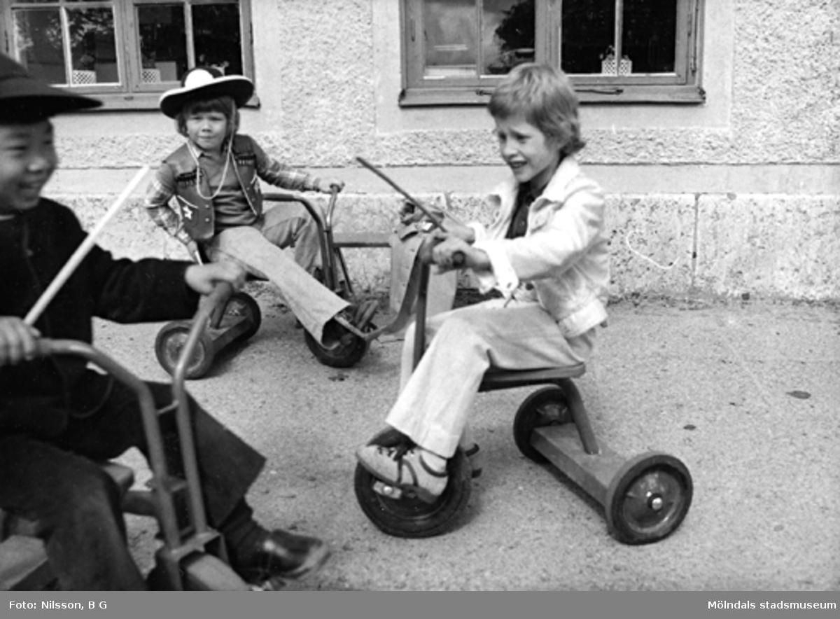 Tre pojkar som cyklar på trehjulingar. Holtermanska daghemmet juni 1974.