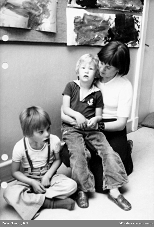 Två barn och en fröken sitter på golvet. Holtermanska daghemmet maj 1975.