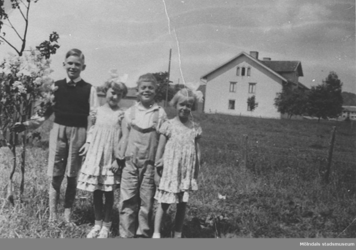 Kompisar hos familjen Elisabet och Oskar Andersson på Bergmansgatan 8, 1935. Från vänster: Rolf, Lill, Åke och Ingegärd Magnusson. I bakgrunden ses Karlsberg på Knutsegatan 15. På denna plats ligger numera Mölndals stadshus.