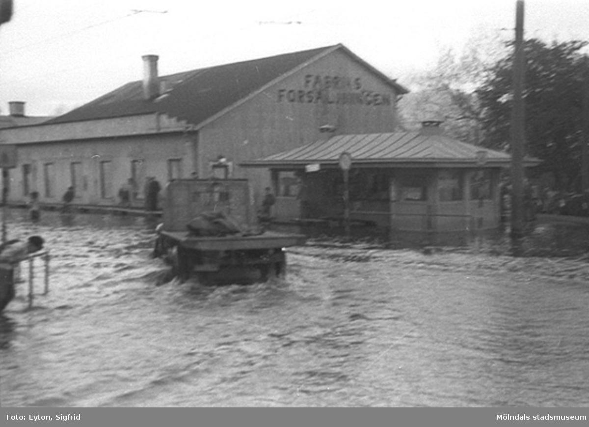 Översvämning vid Fabriksförsäljningen (f. Spårvägshallarna) och Pressbyråns kiosk vid Göteborgsvägen, 1951.Byggnaderna låg i hörnet mellan Kvarnbygatan och Göteborgsvägen.