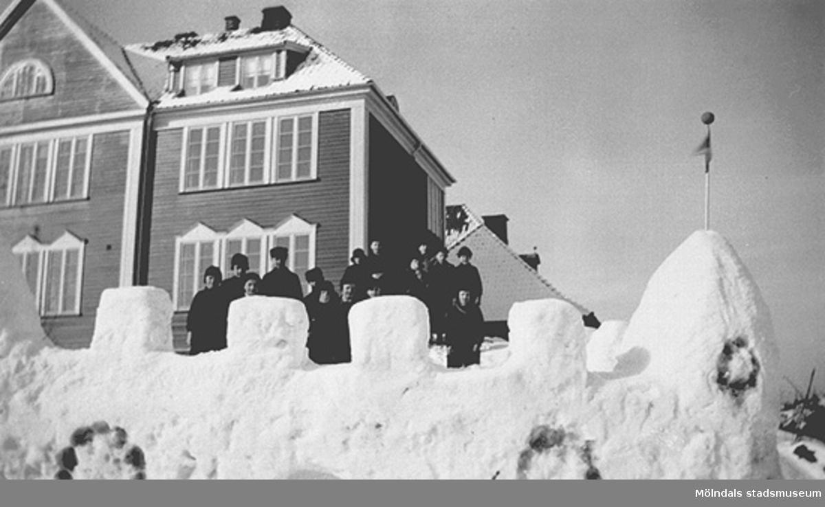 Fjärde året. Lärare: Sven Flodén, Barnen har friluftsdag och har byggt en snöfästning söder om gamla skolbyggnaden. Fotot märkt 4a2 på baksidan.