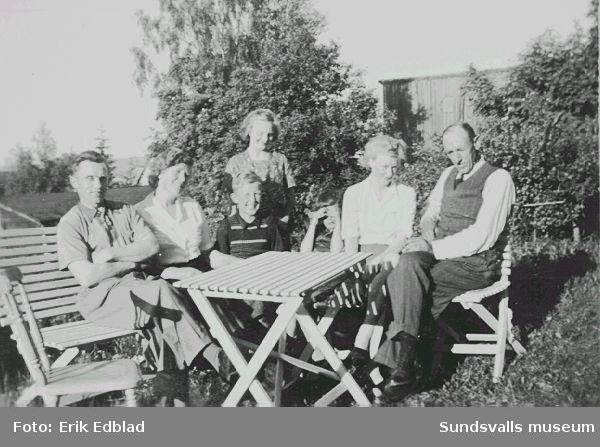 Fr.v. Erik Edblad, Sigrid och Tord Ödlund, Irma och Bernt Edblad, Stina Cramby och Hilding Ödmark i familjen Edmarks trädgård, Södermalmsgatan 8, midsommaren 1946. Sigrid Ödmark var moster och Stina Cramby syster till Siri Edmark. Familjen bodde här 1939 - 1960. Fastigheten ägdes av Helfrid Renström, som bodde i husets undervåning.