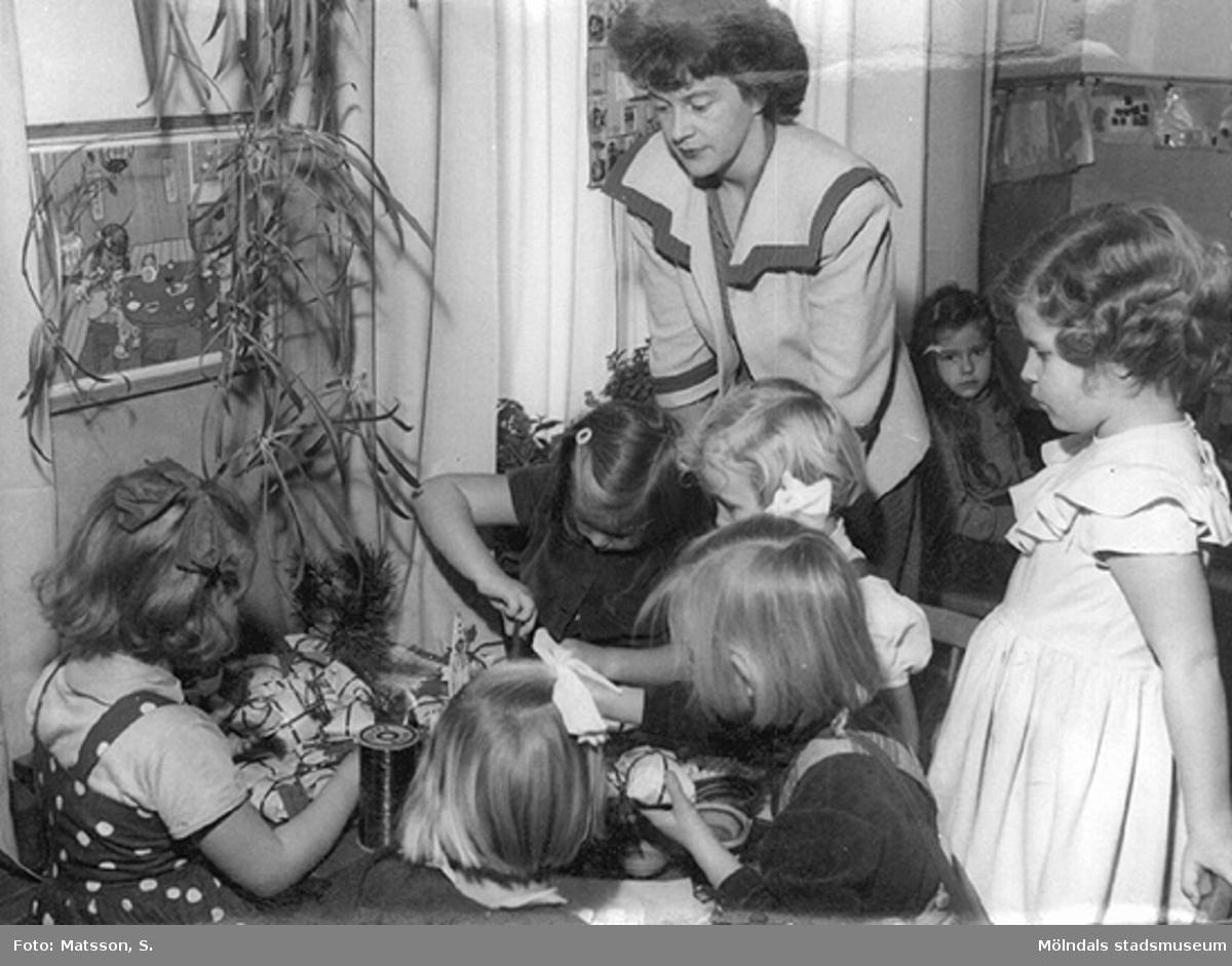 Margit och förskolebarnen slår in julklappar på Hertagårdens barnträdgård i Borås, år 1952.