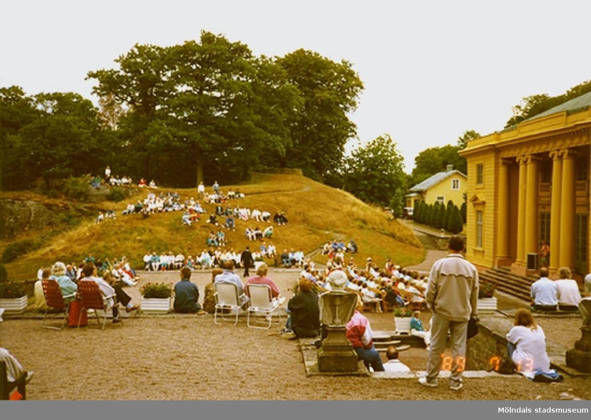 Publik som sitter på gräset samt på stolar och lyssnar på musik.