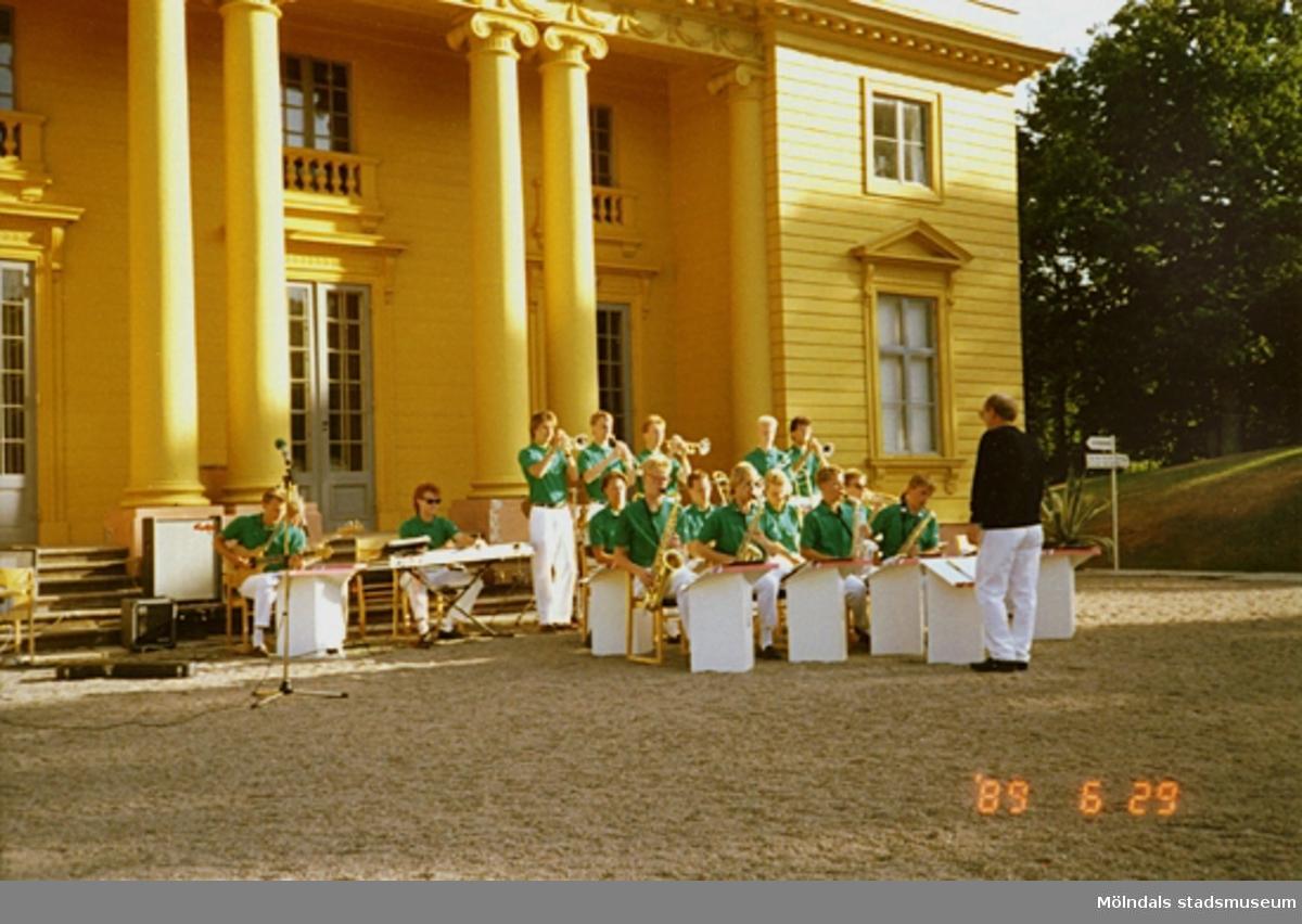 Vy från nordost på musikunderhållning av ungdomsorkester som pågår framför slottet. Musikerna är iklädda vita byxor och gröna tröjor.