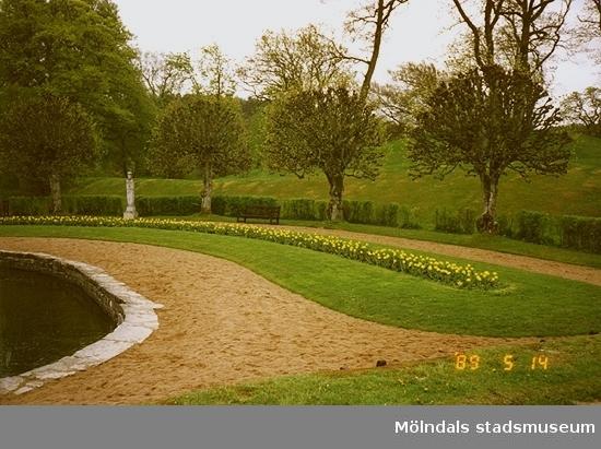 Till vänster ses en del av dammen. Till höger ses parken med träd, blomsterrabatt, en skulptur och grusgångar.