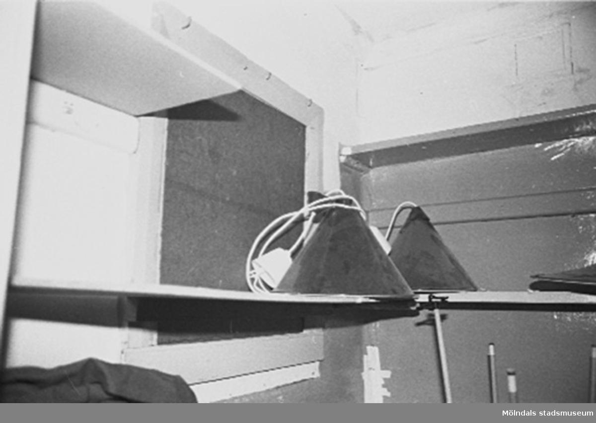 Interiör i fabriksbyggnad. Hylla med lampor.