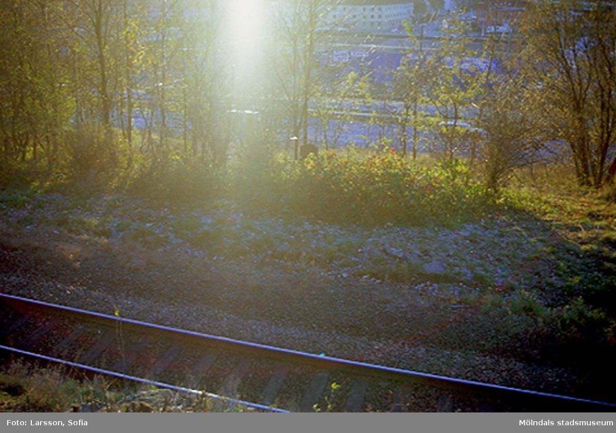 Järnvägsspår som passerar vid Hejderidarens gravsten. I bakgrundens mitt skymtar lägenheter som ligger längst ner på Krokslätts Parkgata.
