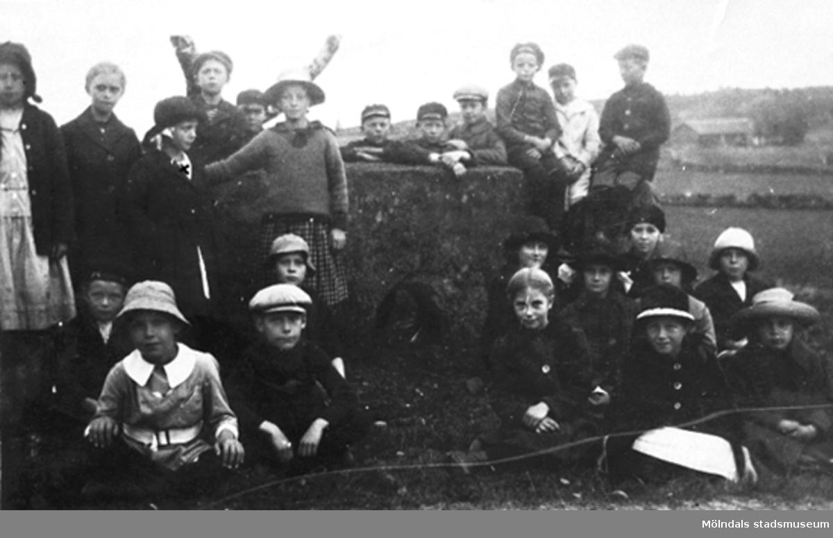 """Skolelever från Liveredsskolan i Kållered, år 1921. Barnen är på utflykt till hällkistan """"Dvärgahuset"""" i Dvärred. Tredje barnet stående från vänster, flickan med mörk hatt, är Rosa Krantz (gift Pettersson)."""