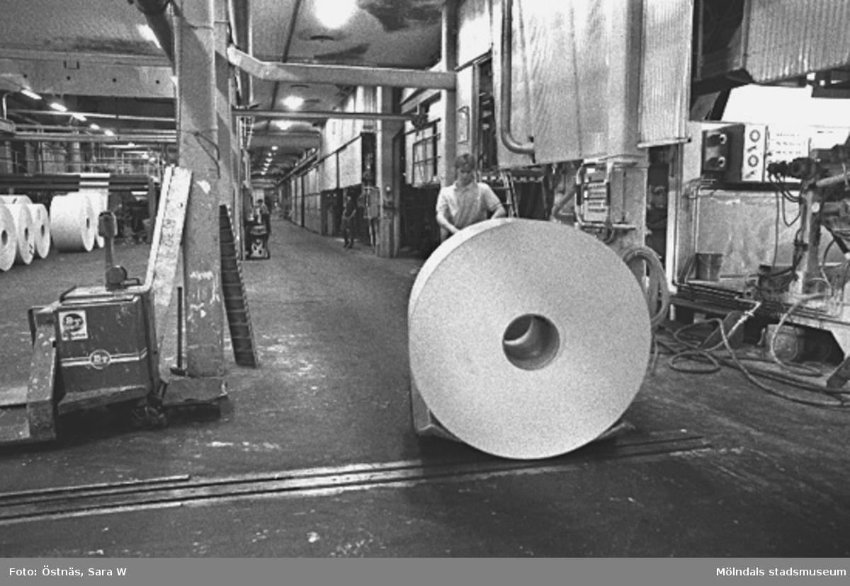 En arbetare med en pappersbal.Bilden ingår i serie från produktion och interiör på pappersindustrin Papyrus.