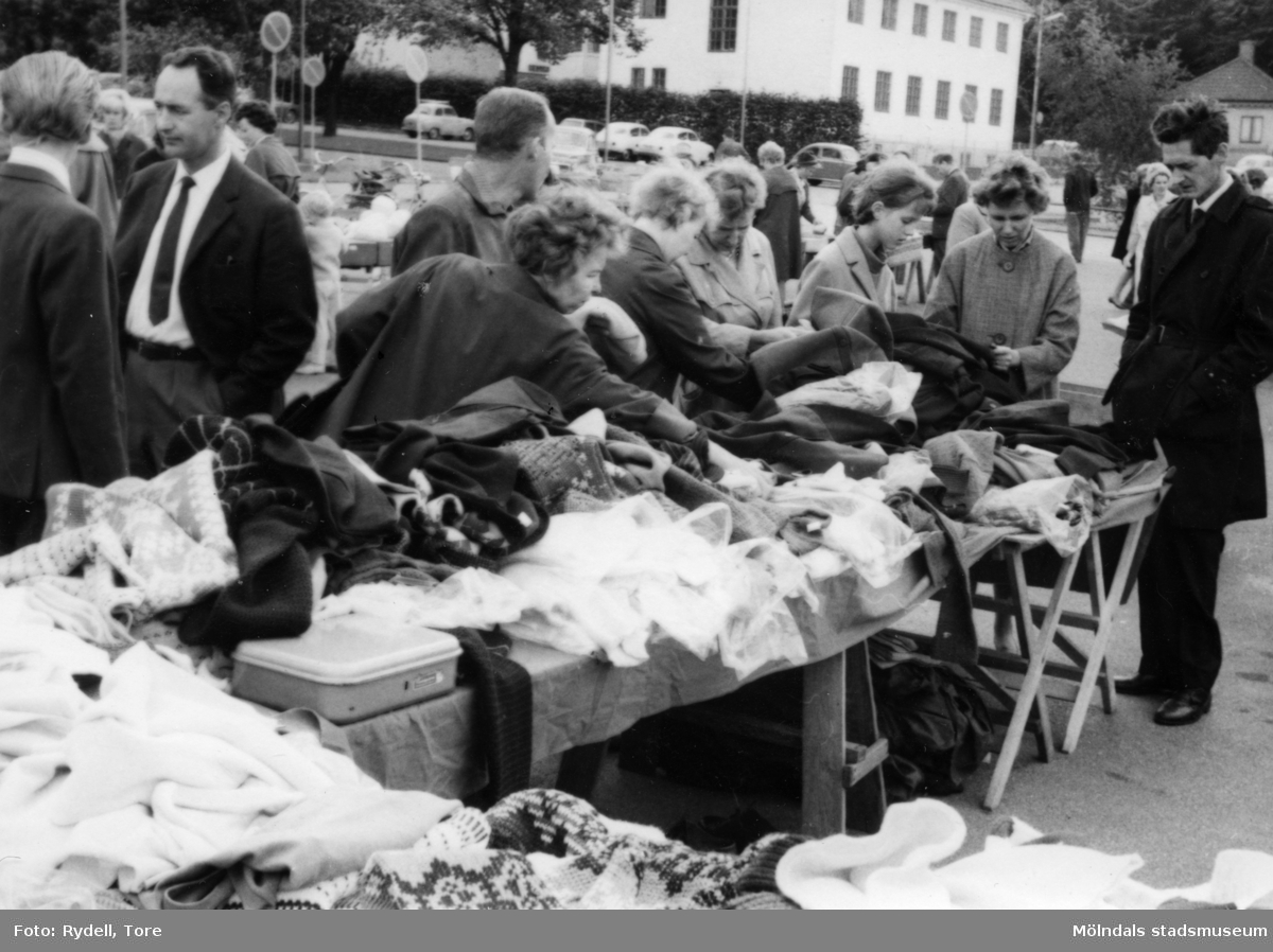 """Vad kostar jumpern?"" Torghandel på Nya Torget i Trädgården, Mölndal, på 1960-talet. I fonden syns gamla apoteket."