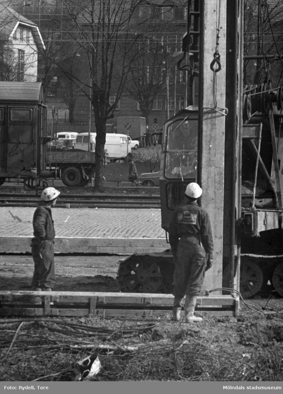 Pålning vid Kvarnbygatan 1967.Fotografi ur album som tillhört Christina Rydell. Bilderna i albumen är delvis från Papyrus där Christinas far Tore Rydell arbetade, men också från Kvarnbyn, Ryet och folkliv i Mölndal. Tore tog ofta med sig kameran till Papyrus där han fotograferade sina arbetskamrater i arbete, men också fester och föreningsliv.