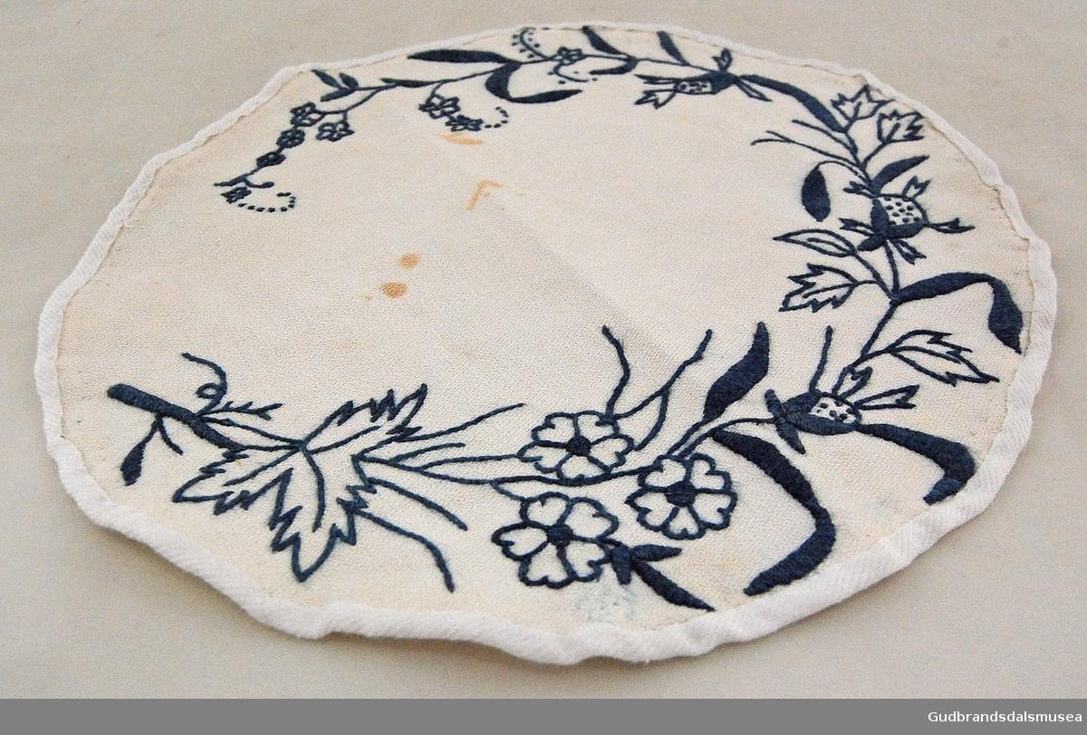 Rund brikke i beige/hvitt med broderte blomster- og bladmotiv i mørkeblått. Dette motivet følger kanten rundt. Påsydd ytre, hvit kant.