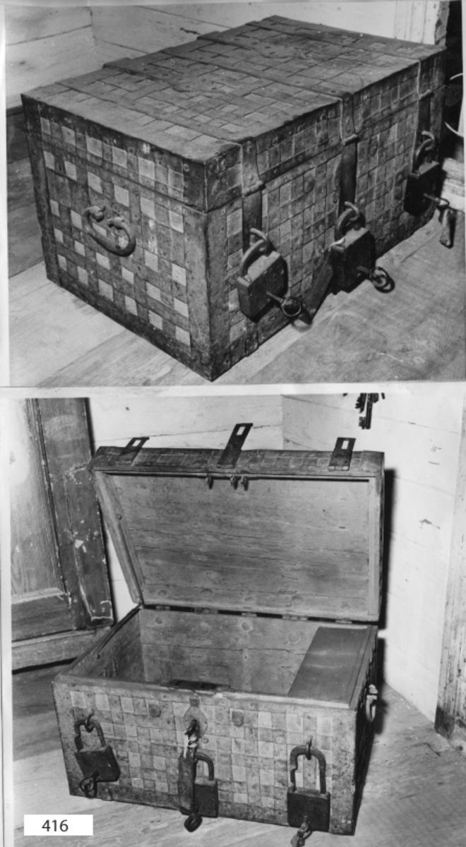 Kassakista, av trä, järnbeslagen och gråmålad samt försedd med 3 st olika hänglås. Den har i botten skruvhål för att kunna skruvas fast i golvet.