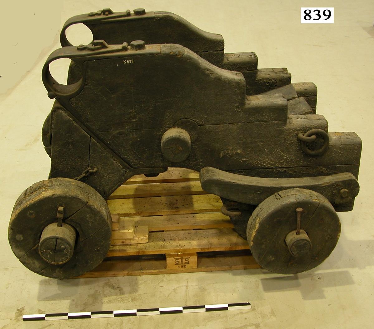 12 cm marschallslavett med tillhörande transportlavett, av trä, svartmålad. Tillkom på inventarium år 1903.