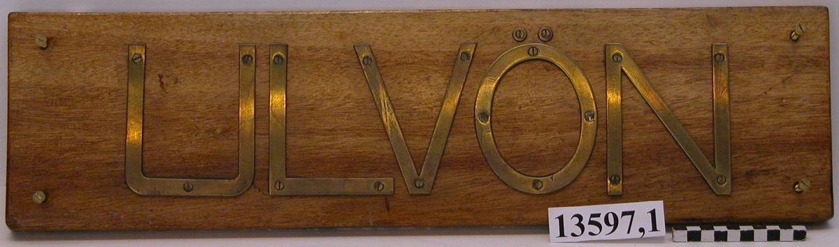 """Bokstäverna av mässing bildande namnet""""Ulvön"""" fastsatta med skruvar på en träplatta. Neg,nr 5925."""