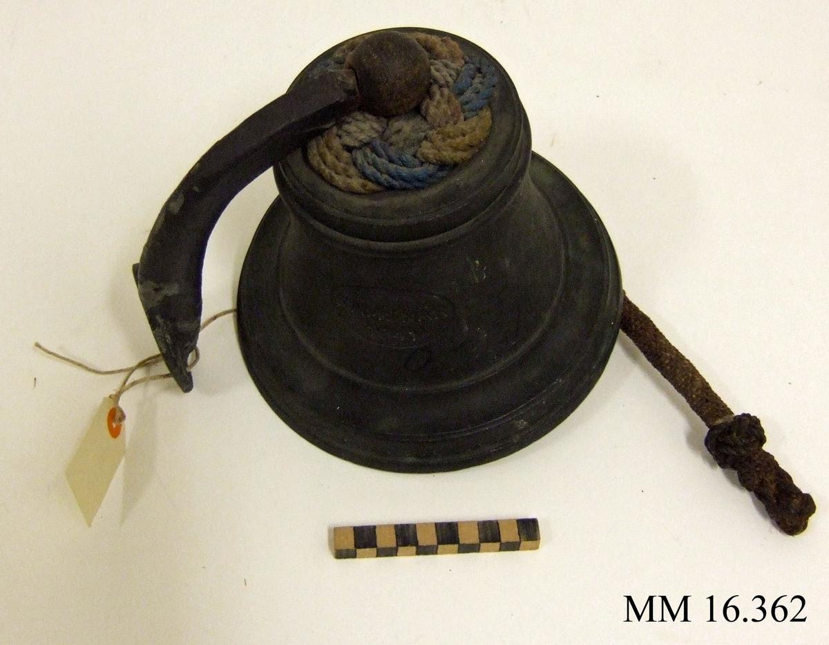 Skeppsklocka av malm. Märkning Ramskär 1941. Komplett med kläpp och upphängningsanordning. Klockan försedd med mönsterbård längs nederkanten.