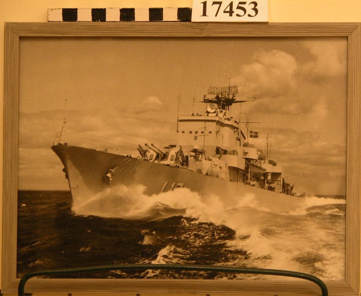 Svartvitt fotografi inom glas och ram visande jagaren Uppland under gång till havs, sedd från babord. Fotografiet är inramat i randad, gråmålad träram, B= 10mm. Baksidan klädd med kartong.