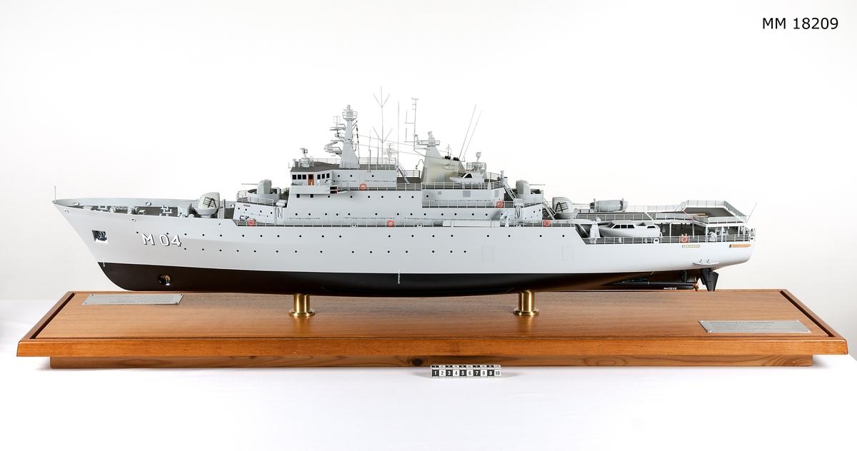 """Fartygsmodell av metall och trä föreställande minfartyget Carlskrona placerad i monter. Målad i ljus grått, svart under kölvattenlinjen. Två propellrar i mässing och två roder. Skråvet har två rader ventiler, i fören målat med vitt """" M 01 """". Däcket är mörkgrått. Livbåtar, i aktern helikopterplattform märkt med stort orange H. Luftvärnspjäser i för och akter, antenner. Modellen är placerad i monter bestående av rektangulär teakplatta med glashuva och är fästad till plattan med hjäp av två hållare av mässing. På plattan finns två metallplattor med graverad text placerad på vardera kortsida, samma text på båda plattorna. """"Minfartyget Carlskrona, leverantör Karlskronavarvet AB, leveransår 1982, Byggt för försvarets materielverk, Längd överallt 105,70 m, Bredd mallad 15,20 m, Djupgåend mallat till KVL 4,00 m, Deplacement till KVL inkl. bihang och bordl. 3138 kubikmeter, Maskinstyrka 4 x 1940 k W."""" Monterns mått: H = 420 mm  L = 1170 mm B = 260 mm"""