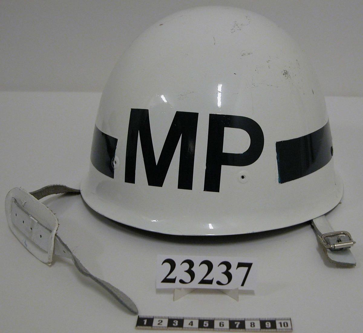 """Vit hjälm av plast som försetts med militärpolisbeteckning genom att bokstavssätten MP i blått fäst på hjälmen. Bokstavssätten är gjorda i självhäftande plast och består av bokstäverna M och P samt ett bågformat 40 mm brett band. M och P är placerade mitt fram på hjälmen och det 40 mm breda bandet löper runt hjälmen 2 cm från kanten. Hakrem av vitt läder med förnicklat spänne. Hjäminredning av plast, svettrem av naturfärgat läder, stämplad 59 -63 och hjässband av textil. På hjälmens insida , gjutet i plasten """" Tre konor Gr.75 SW 75, samt vit tejp med siffrorna 616 i blått"""