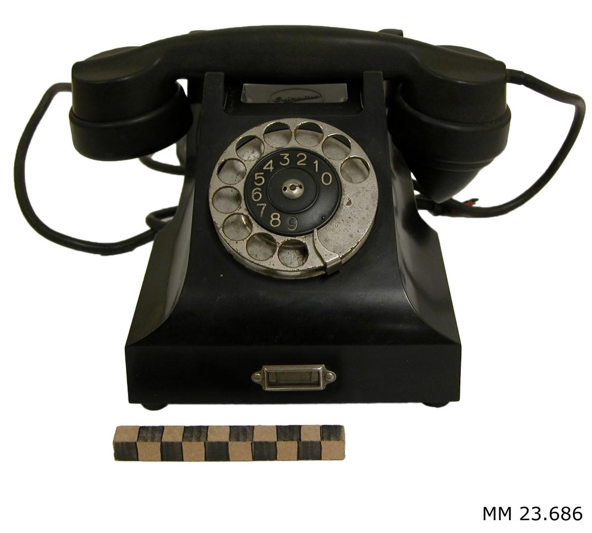 Telefon av svart bakelit försedd med sladdar av gummi. Telefonklykorna är av metall. Fingerskiva av metall, försedd med numreringarna 0-9 i vitt på svart plastskiva. Under luren finns L M Ericssons logotype. Sladd mellan lur och telefonapparat av svart gummi. Sladd mellan telefonapparat och vägg av svart gummi. Sladd till vägg saknar kontakt.
