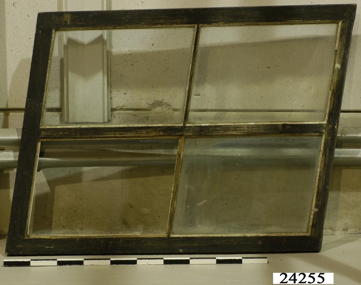 Spröjsat fönster med tre glas (ett glas saknas) inom snedvinklad ram av trä. Ramen har svartmålad utsida och gråmålad insida. Vitt kitt runt glasrutorna.