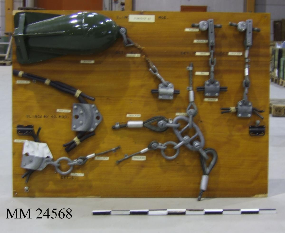 Undervisningstavla försedd med olika exemplar av kablar (såsom minsvep och svepkablar) använda av Flottan. Upphängningsbar.