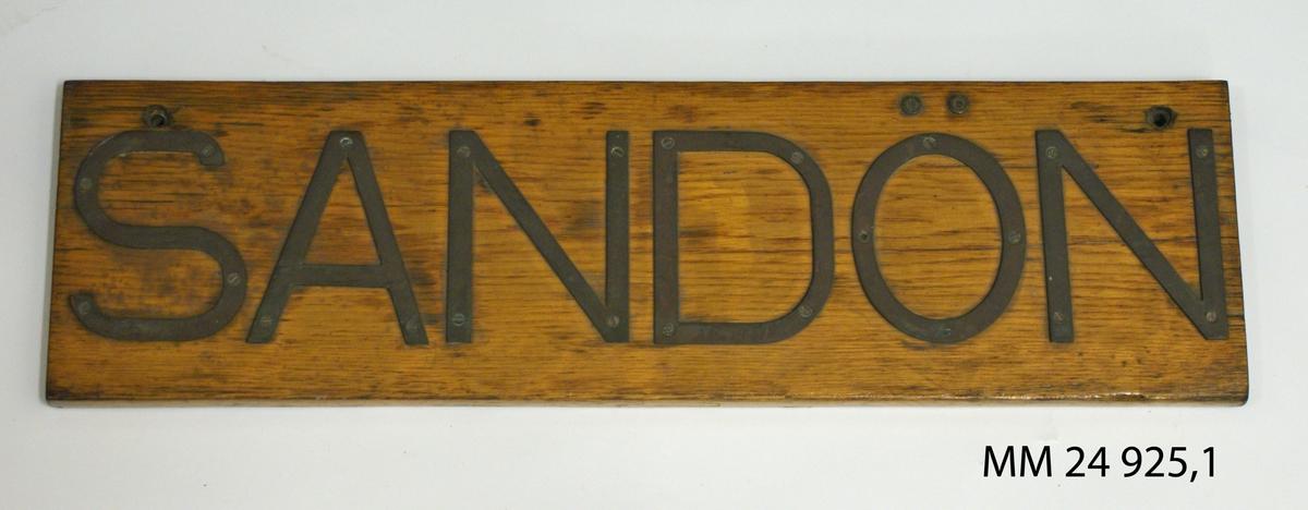 """Namnbräda av fernissad treak. Bokstäver av mässing fastskruvade från framsidan, bildar namnet: """"Sandön""""."""