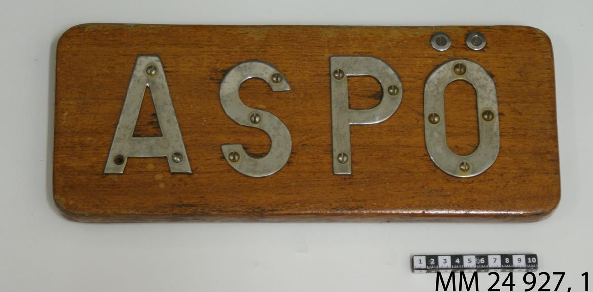 """Namnbräda av fernissad teak. Bokstäver av stål fastskruvade från framsidan, bildar namnet: """"Aspö""""."""