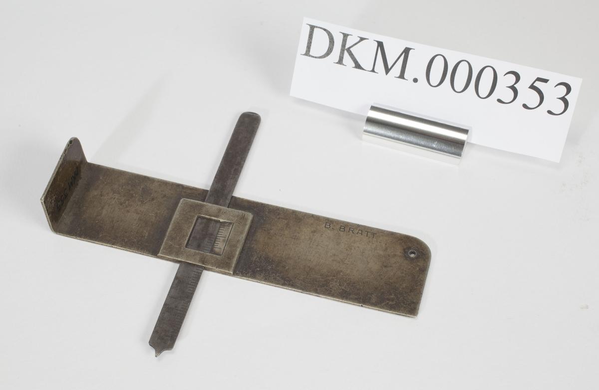 Dybdemål med skala merket til 40 mm festet på større stålplate.