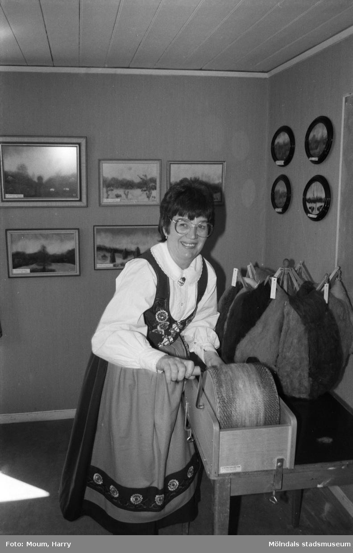 Kerstin Söderlund ställer ut i ABF-stugan i Lindome, år 1984. Kerstin Söderlund vid specialkardan. I bakgrunden hennes tavlor.  För mer information om bilden se under tilläggsinformation.
