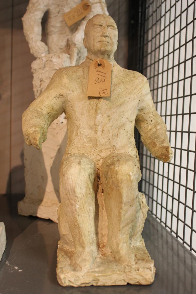 Skulptur i gips av en sittende mann.