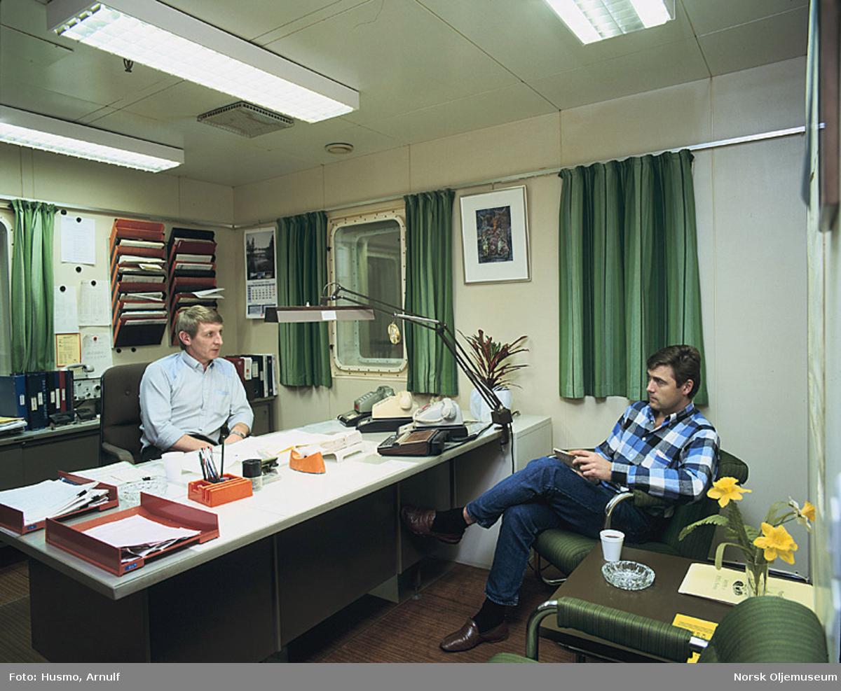 """Administrasjonsleder offshore, Knut Lorentzen i samtale med en annen mann på sitt kontor i 5. etasje (feltadministrasjonen) på """"Ekofisk 2/4 Hotellet""""."""
