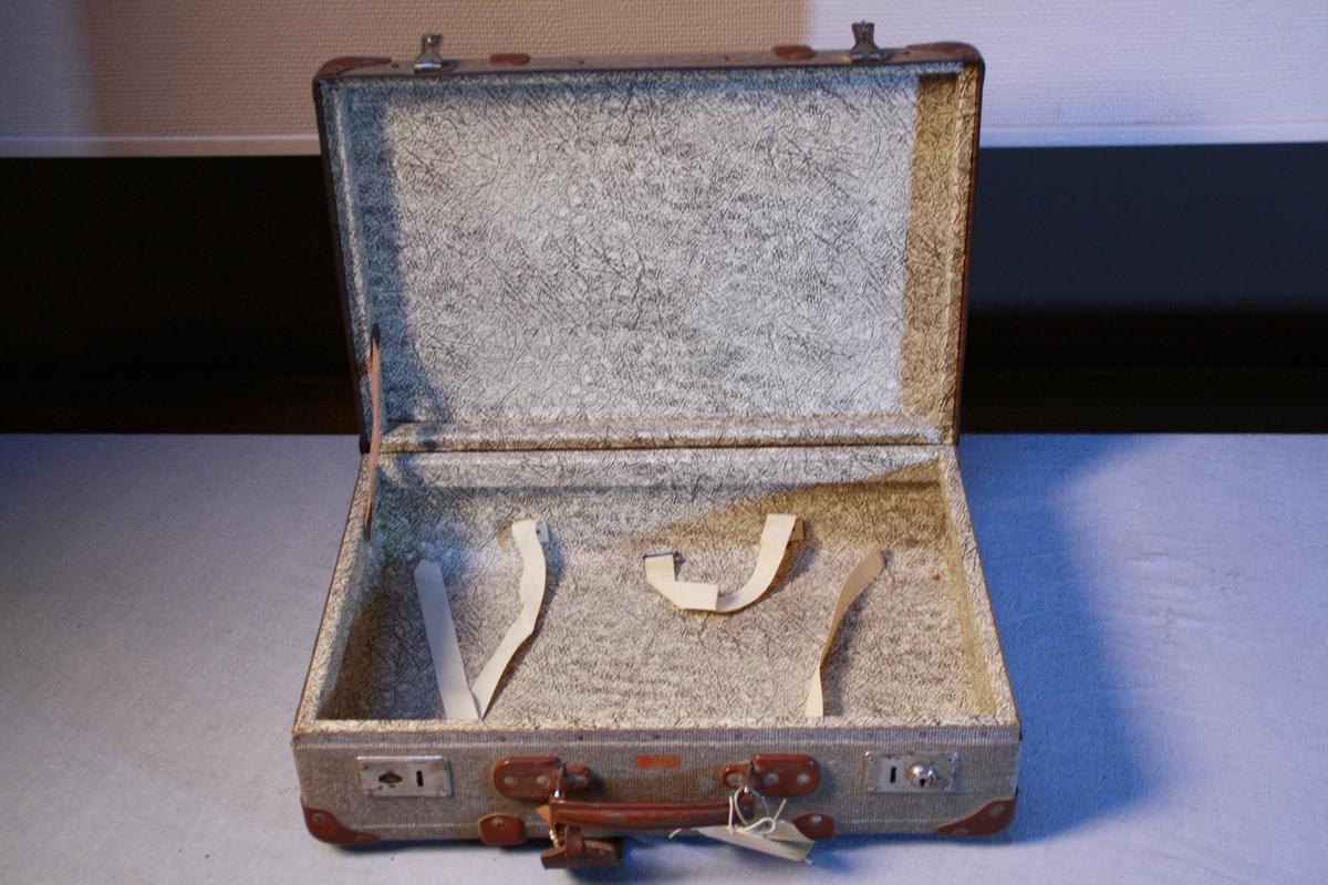 Koffert i vulkan fiber. Forsterka hjørner, handtak og to låser. Sett saman med naglar. Trekt med mønstrete papir inni. Festestropper. Adresselapp.