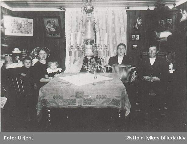 Stueinteriør og familie på fem, Ørje i Marker,  ca 1920. Fra Brakka hos familien Jensen ca. 1920. Far ansatt på Ørje Brug.  Fra venstre Dagfinn, Olga,  Lilly (på fanget, født 1916) og August Jensen.  vt. Jens Eliassen og Anders(?).