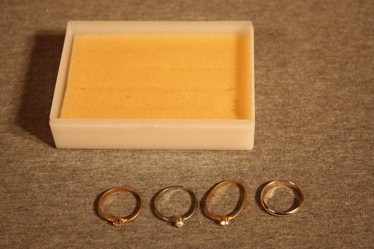 Lita plastøskje med 4 fingerringar - ein glatt og tre med glasperle. Ringane står i skumgummi