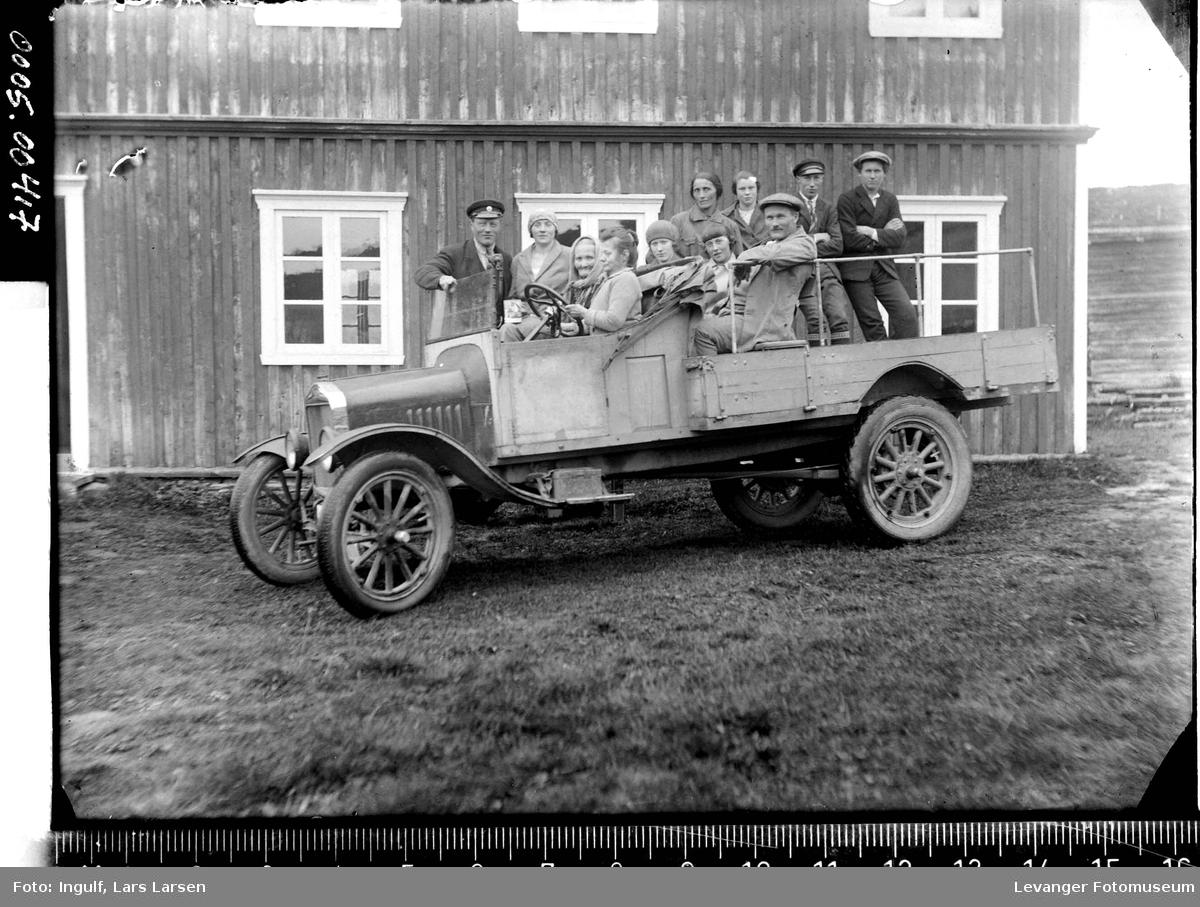 Lastebil med rned en gruppe mennesker i førehuset og på lasteplanet,  bilden er en Ford TT ca 1924-27,