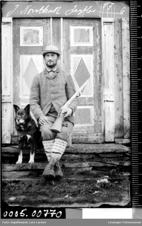 Portrett av mann med gevær og hund.