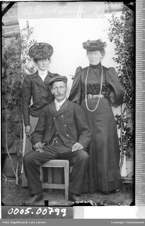 Portrett av to kvinner og en mann.
