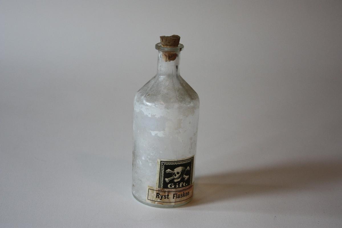 Rund flaske med kork. Har innehalde væske med kvitt tørrstoff. Merkt med giftmerke og stempel Gift Ryst flasken. Sjå SUM.10888.