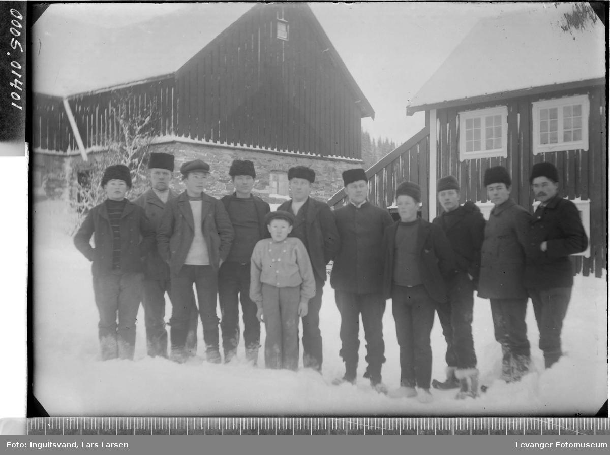 Gruppebilde av ti menn og en gutt på et gårdstun.
