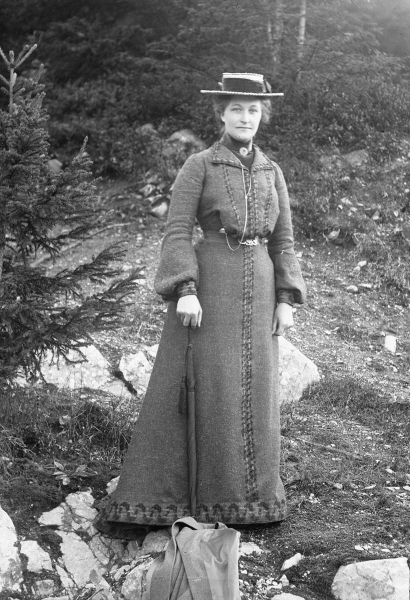Kvinne i helfigur med hatt og paraply, i skog
