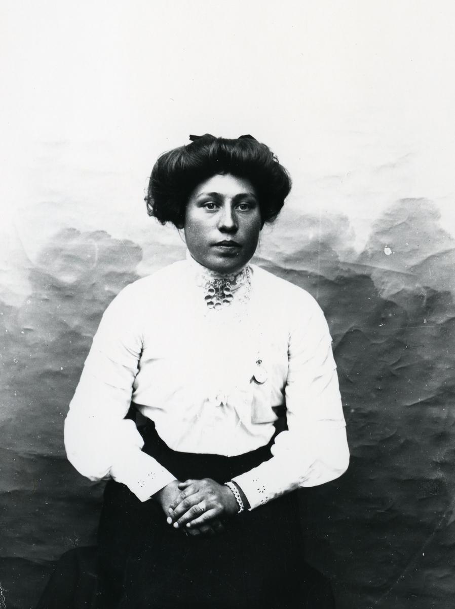 Kvinne kledd i hvit bluse og sølje, fotografert i halvfigur foran lerret
