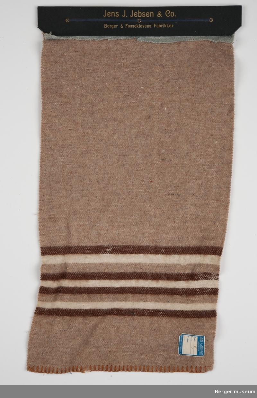 En prøve. En blå prøve er klippet av. Ensfarget brun med triper i mørk brun og hvit offwhite. Designet er eldre enn prøven. Prøvene er festet sammen med papp og snor.
