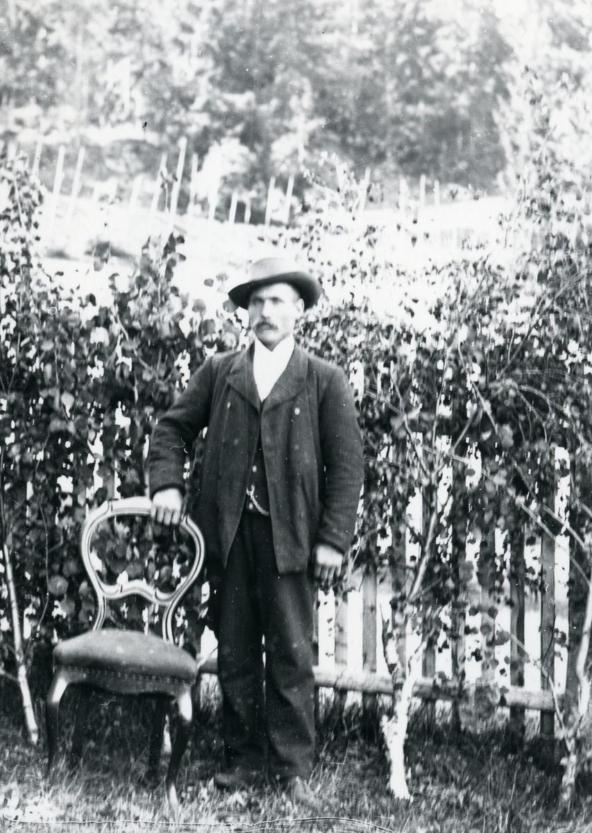 Mann i helfigur foran bjørkekvister og stakittgjerde, stående ved stol