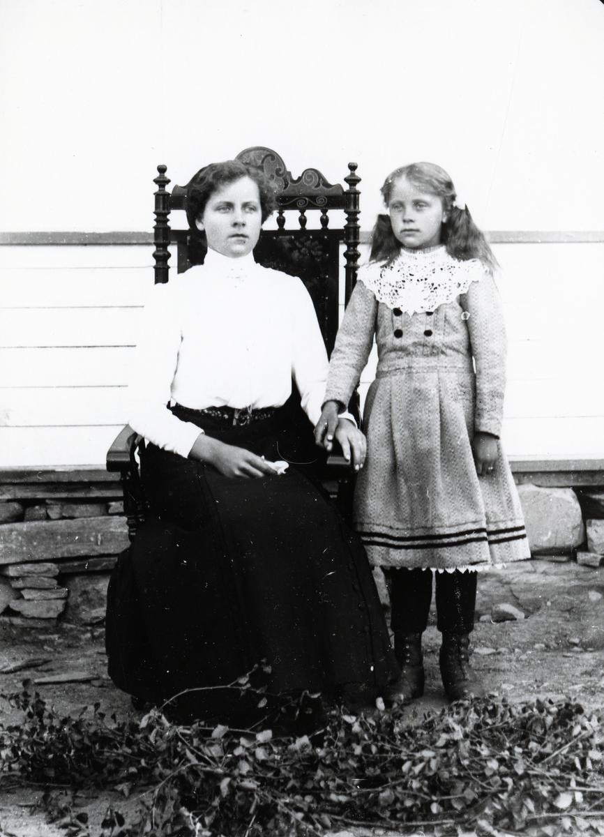 Kvinne i gyngestol og jente stående ved siden av, foran husvegg