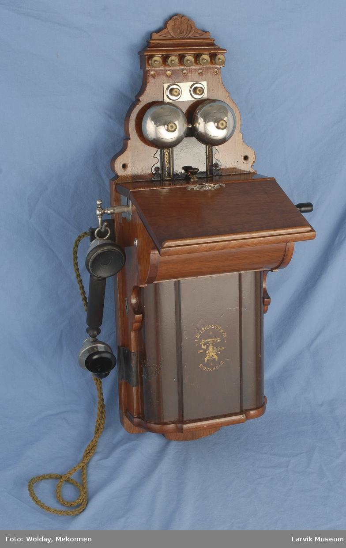Form: Telefon kasse med lokk til å åpne. Telefon røret henger på venstre side. Sveiv på høyre siden.    Manuell